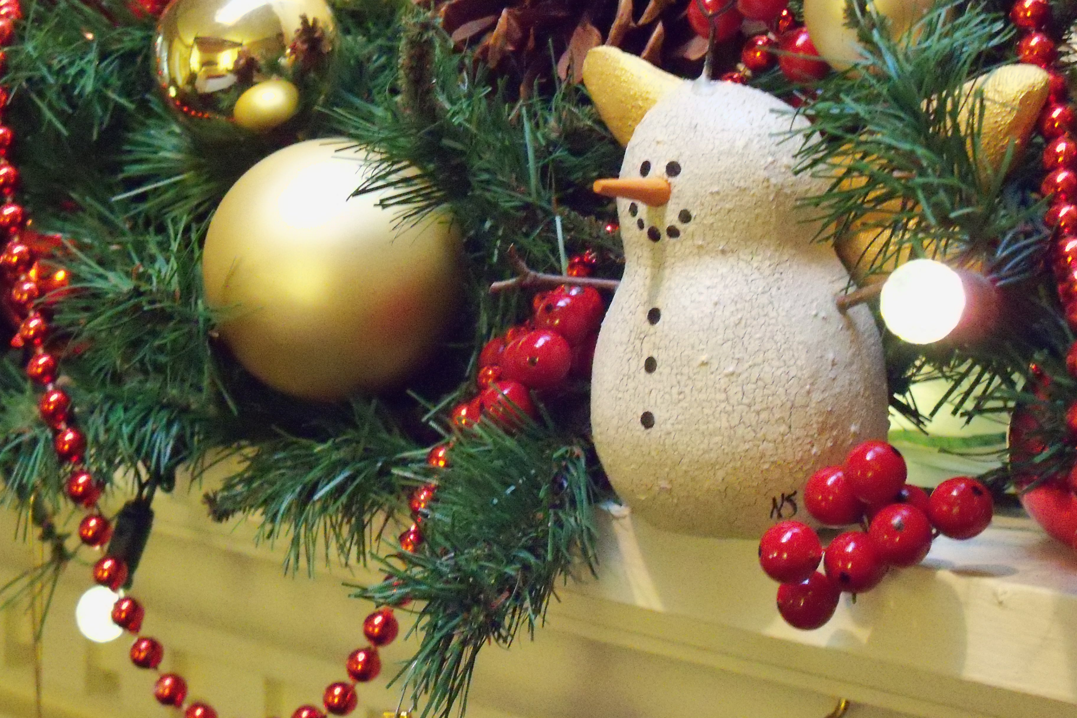 Decorative snowman ornament on decorative christmas mantle top of garland and cranberries with gold balls and lights.