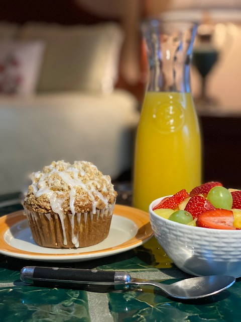 A Banana Streusel Muffin on a table next to bowl of strawberries, melon, and grapes next to a caraffe of orange juice.