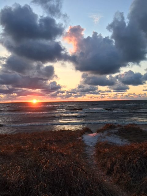 View from beach over water with setting sun's orange rays reflecting off of pillowy clouds and whitecapped waves.