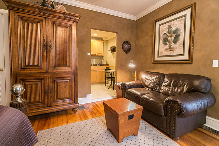 Brown leather couch with armoire and kitchen in the corner.