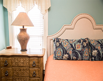 Bed with peach comforter, tufted headboard, and lamp sitting on bedside dresser in front of window.