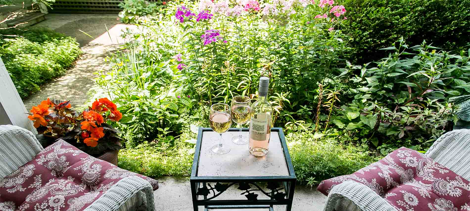 Table with two wine glasses and bottle of pink wine. Wicker chairs sitting next to it.