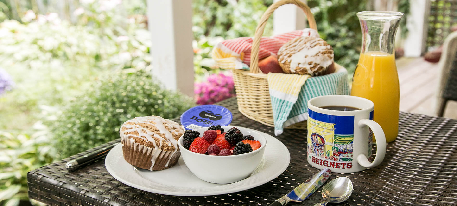 Mixed berries with muffin, coffee, orange juice and bread basket.