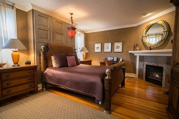 Bed with purple comforter, hardwood floors and grey stone fireplace in corner.
