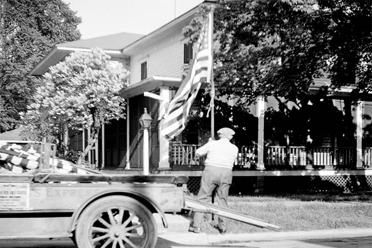 Old picture with man putting up flag in front of old house and car.