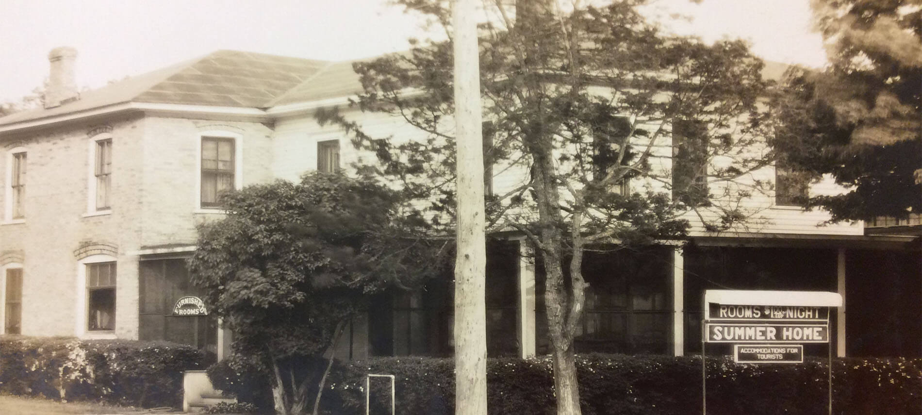Old photo of hotel or bed and breakfast with sign for rooms. Name on sign is Summer Home.