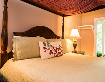 Four-Post canopy bed with burgandy drape hanging over beige bedspread and decorative pillows with lamp on bedside table.