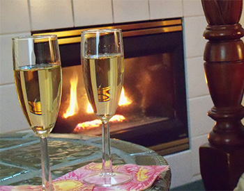 Full champange glasses in front of roaring fireplace on glass table.