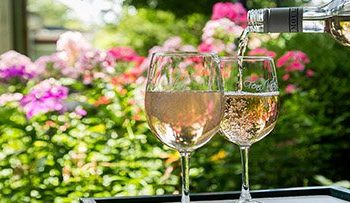 Wine being poured into two wine glasses with a backdrop of flowers.