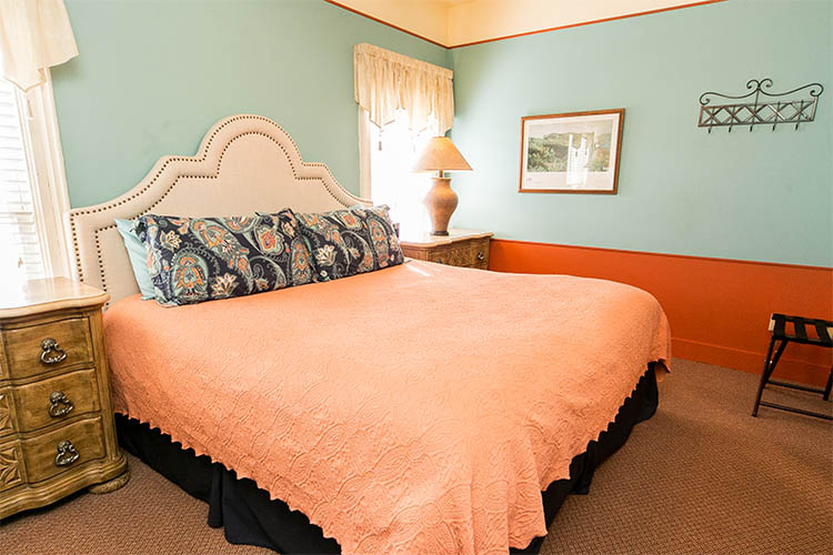 King size bed with peach comforter and tufted headboard. Two nightstands with lamps.