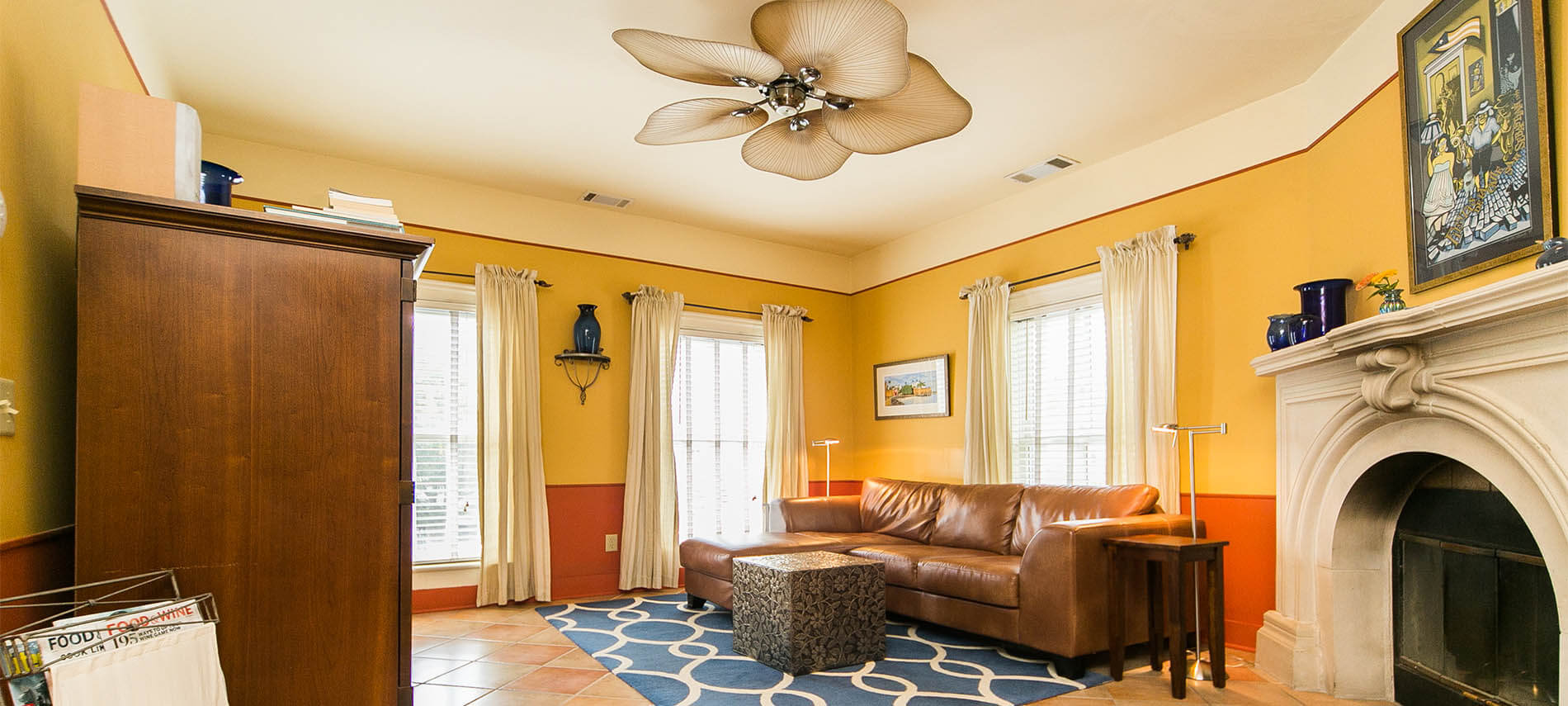 Brown leather couch with blue run that had round rings in it and a white stone fireplace and unique fan.