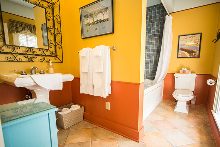 Yellow and orange bathroom with blue tiles shower and square sink.