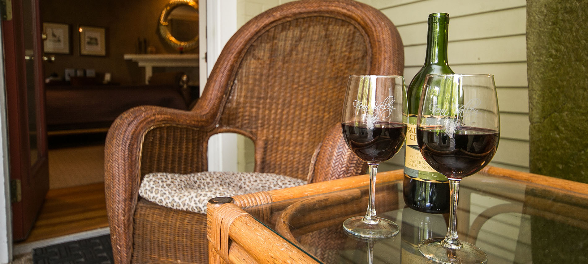 Wine bottle and two glasses of wine sitting next to a wicker chair with door to room open.