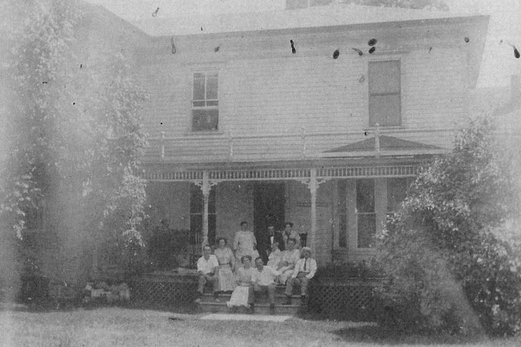 Old photo of family and friends sitting on front porch with arms around each other.