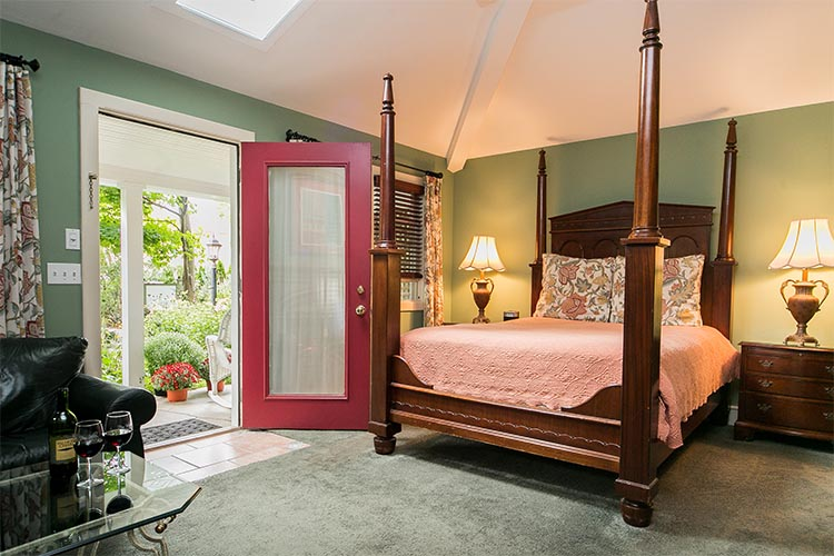 Four poster bed with peach comforter and flowered bed pillows. Leather couch in the corner.